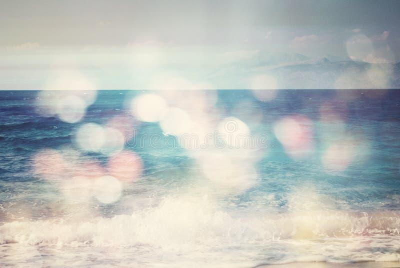 Bakgrund av den suddiga stranden och havet vinkar med bokehljus royaltyfri bild