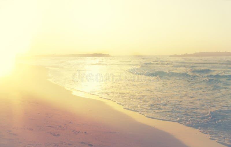 Bakgrund av den suddiga stranden och havet vinkar, tappningfiltret royaltyfria foton