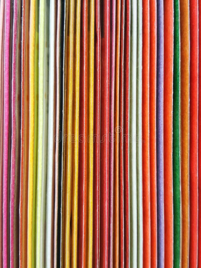 Bakgrund av färgrika inbindningsanteckningsböcker är ordnad på en bokhylla royaltyfri bild