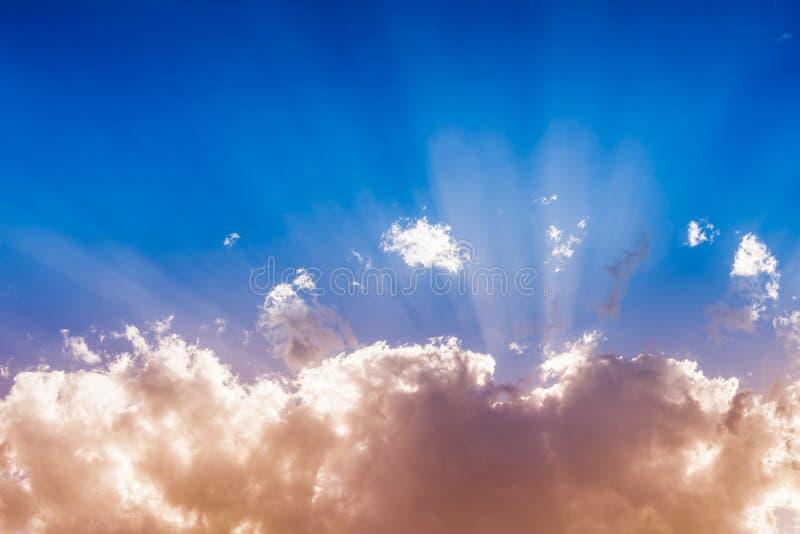 Bakgrund av färgrika moln, solen bak molnen och solstrålar i himlen arkivbild