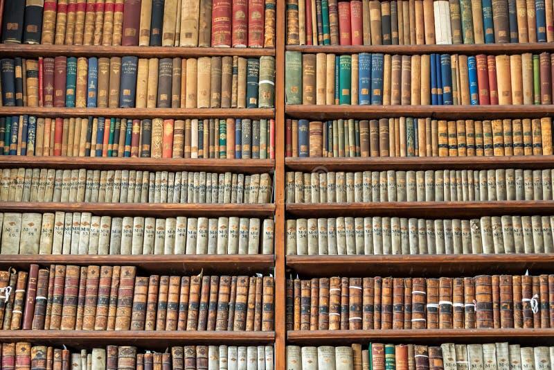 Bakgrund av gammal tappning bokar på den wood bokhyllan i ett arkiv arkivfoton