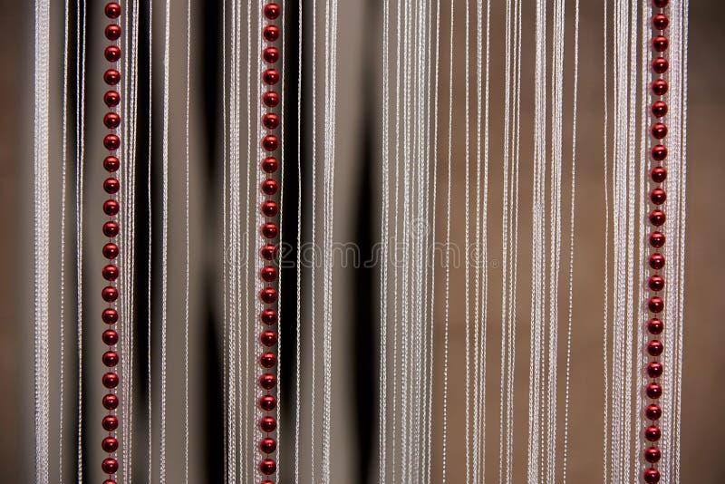 Bakgrund av gardiner med vita trådar och röda pärlor arkivbild