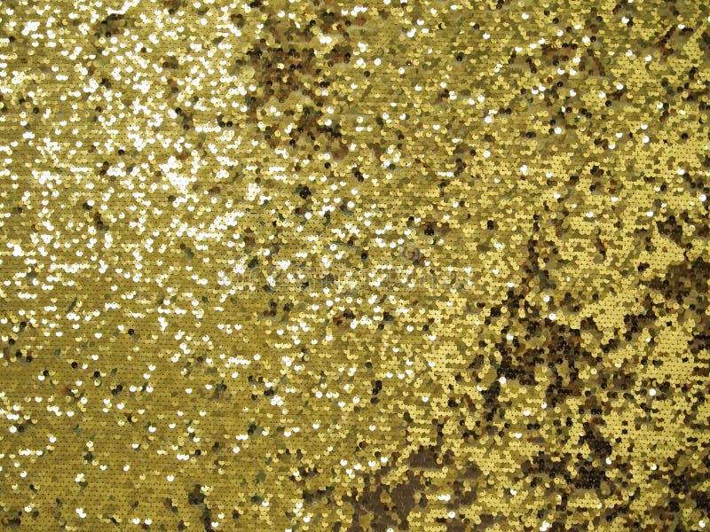 Bakgrund av guld- skinande paljetter arkivbilder