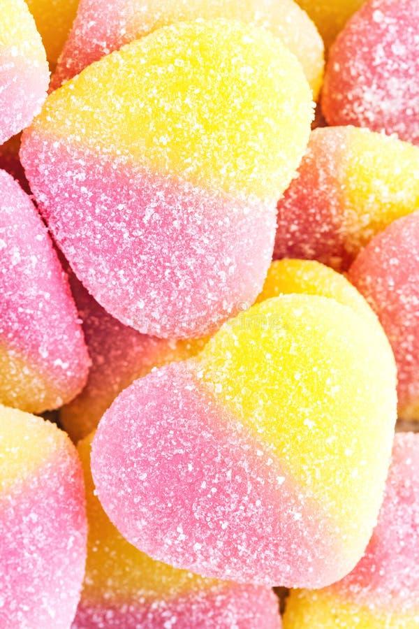 Bakgrund av guling- och rosa färgfruktgodisen i form av hjärta, clo royaltyfria foton