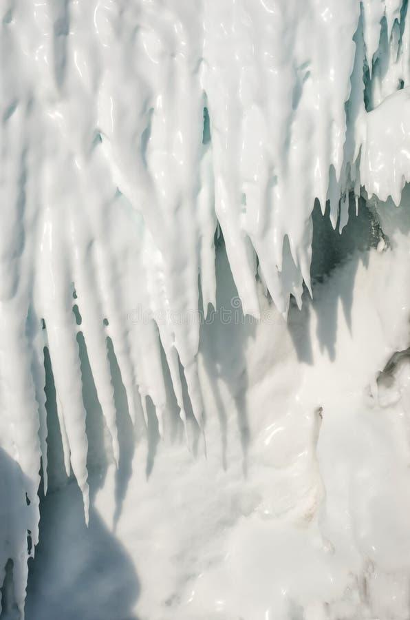 Bakgrund av isstalaktit med en spricka Vita istappar i en djupfryst isvägg royaltyfria foton