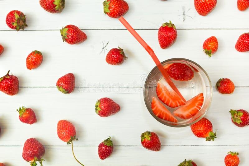 Bakgrund av jordgubbevatten och nya bär på en ljus vit tabell Detox en sund livsstil ny drink royaltyfri foto