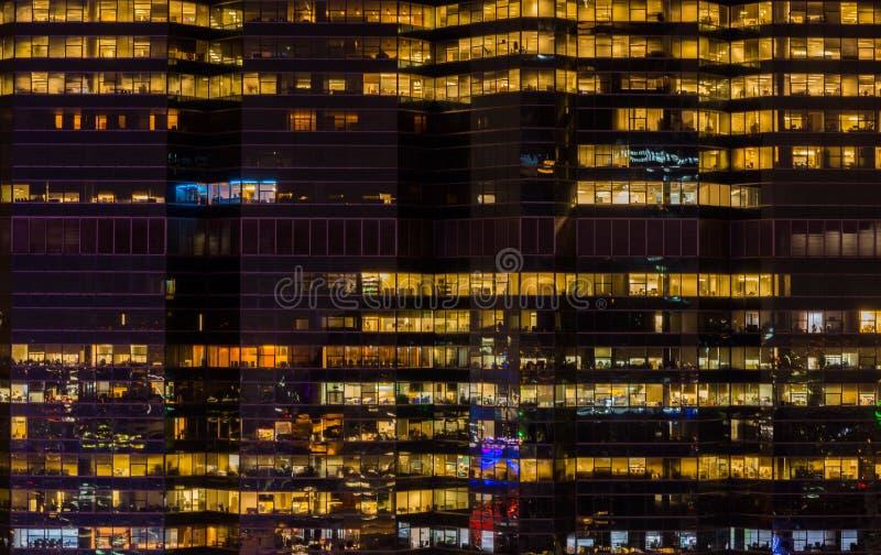 Bakgrund av kontorsbyggnadglöd på natten royaltyfri foto