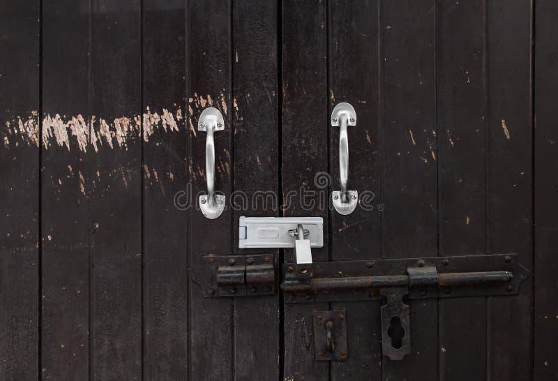 Bakgrund av låste dörren för tappning den trä med skalningsmålarfärg och det rostiga gångjärnet fotografering för bildbyråer