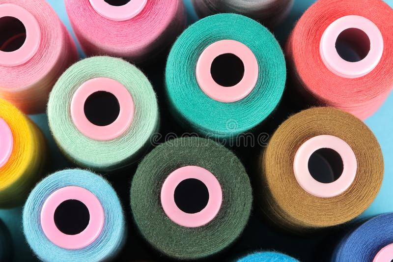 Bakgrund av mång--färgade spolar med tråden, tillbehör för att sy fotografering för bildbyråer