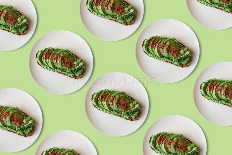 Bakgrund av mycket läckra och näringsrika veggierostade bröd eller smörgåsar med avokadot och guacamole i ett minsta royaltyfri bild