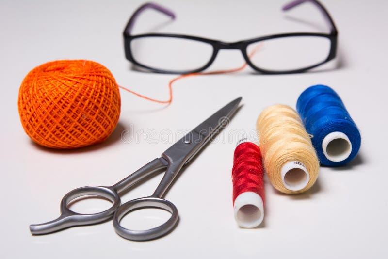 Bakgrund av tråden, exponeringsglas och sax för spole den mångfärgade arkivfoto
