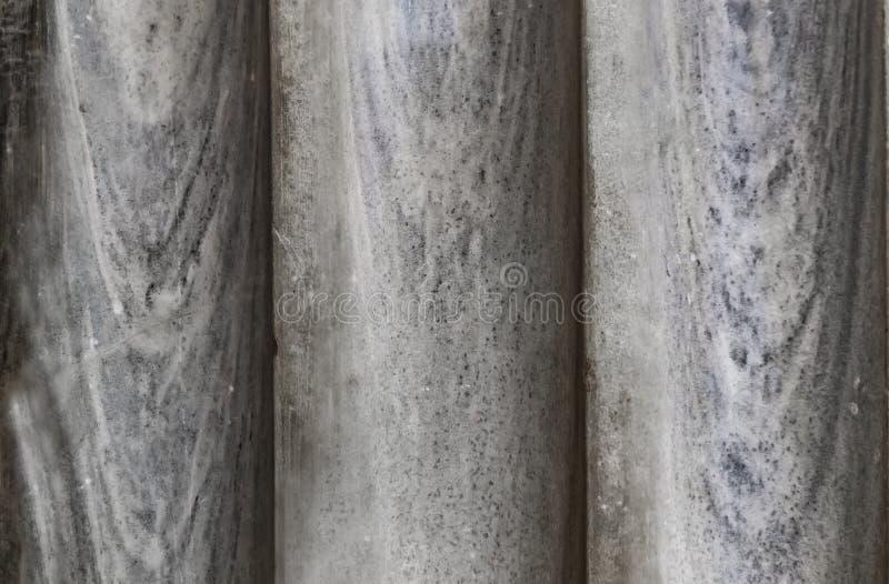 Bakgrund av tre gamla marmorpelare knuffade upp tillsammans - närbilden som var grå med blåa signaler arkivfoton