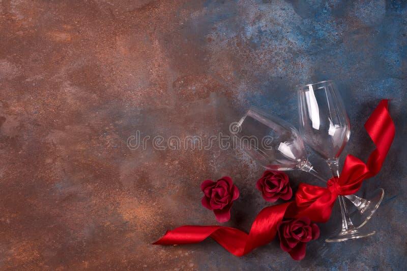 Bakgrund av valentindagberöm med två exponeringsglas, rosor och det röda bandet på stenbakgrund med kopieringsutrymme royaltyfri foto
