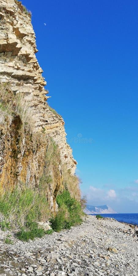 Bakgrund Berglandskap mot den blåa molnfria himlen och havet royaltyfria bilder