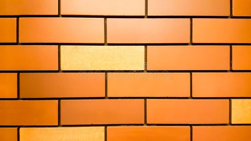 Bakgrund eller textur av den orange tappningtegelstenv?ggen royaltyfri fotografi