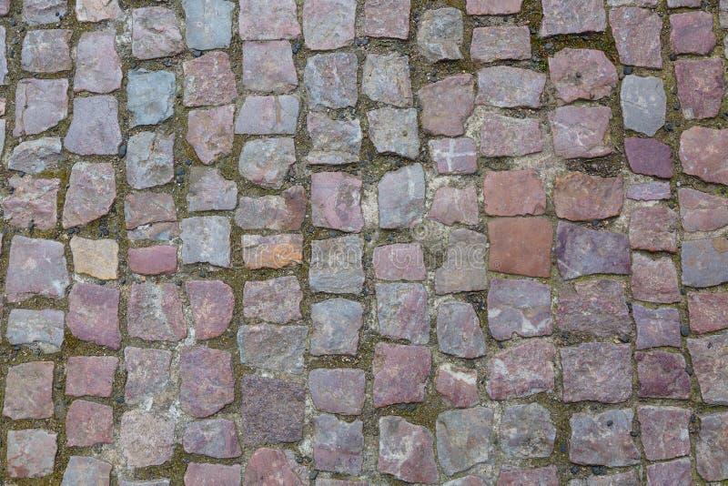 Bakgrund eller textur för trottoar för stengranit cobblestoned Abstrakt bakgrund av den gamla kullerstentrottoarnärbilden i Pragu royaltyfri fotografi