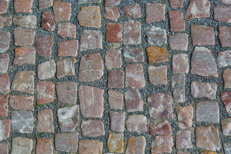 Bakgrund eller textur för trottoar för stengranit cobblestoned Abstrakt bakgrund av den gamla kullerstentrottoarnärbilden i Pragu royaltyfria foton