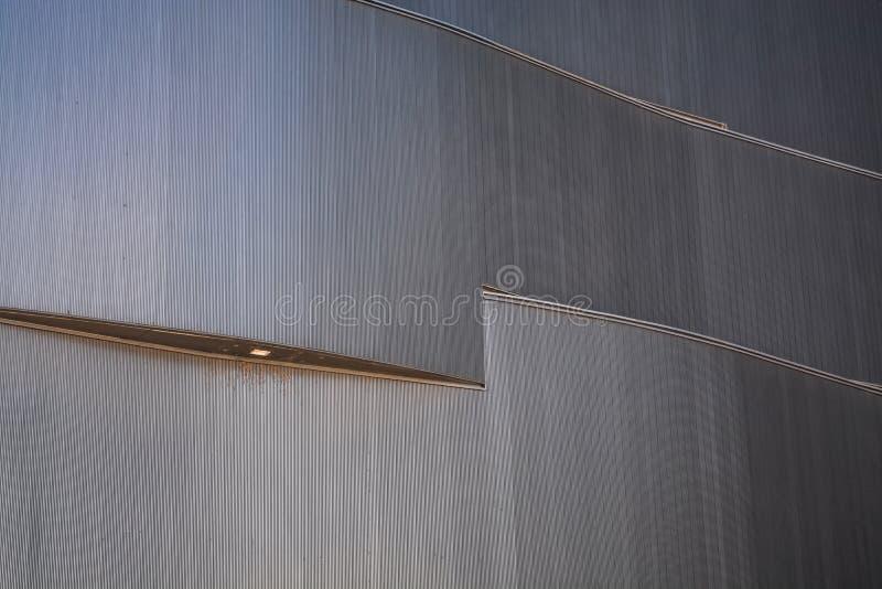 Bakgrund eller textur i form av grå beläggning av fasaden av byggnaden med belysning Geometri av linjer och minimalism arkivfoto
