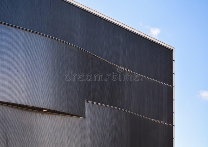 Bakgrund eller textur i form av gr? bel?ggning av fasaden av byggnaden med belysning Geometri av linjer och minimalism arkivbilder