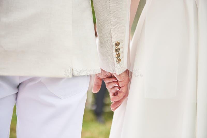 Bakgrund för bröllopdag Det lyckliga parinnehavet räcker tillsammans som för evigtförälskelse arkivfoton