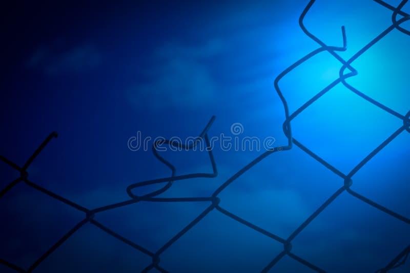 Bakgrund för brutet trådstaket och för blå himmel royaltyfri bild