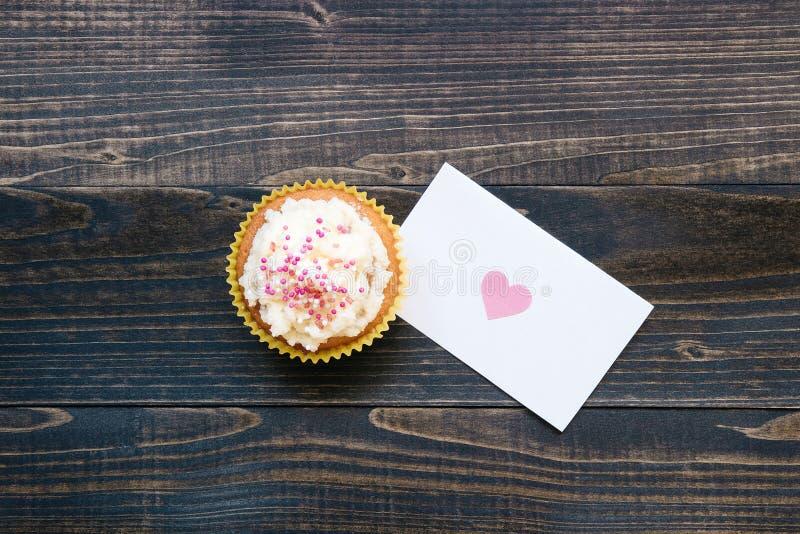 Bakgrund för dag för valentin` s Kort och muffin för dag för valentin` s på den trämörka bakgrunden royaltyfri bild