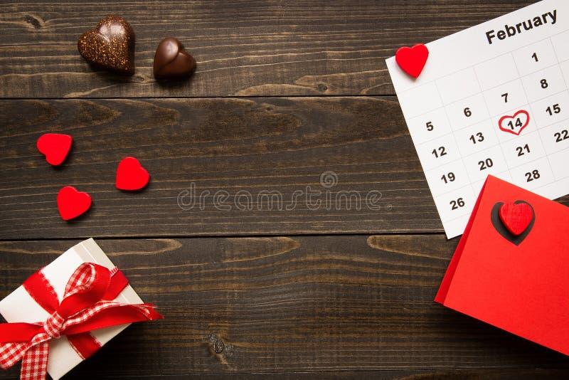 Bakgrund för dag för valentin` s med kopieringsutrymme Kort för dag för valentin` s, gåvaask och choklad på trätabellen arkivfoto