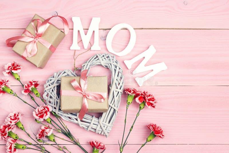 Bakgrund för dag för moder` s med nejlikablommor och gåvaaskar på den rosa trätabellen arkivbild