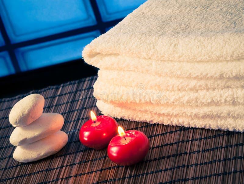 Bakgrund för den Spa massagegränsen med handduken staplade stenen och röda stearinljus varm atmosfär arkivbilder