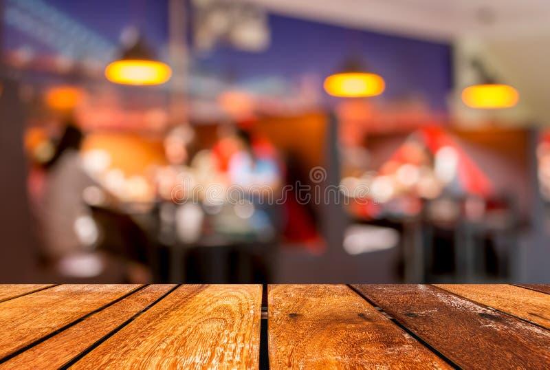 bakgrund för den tom brun trätabellen och coffee shopsuddighet med bokeh avbildar royaltyfria foton