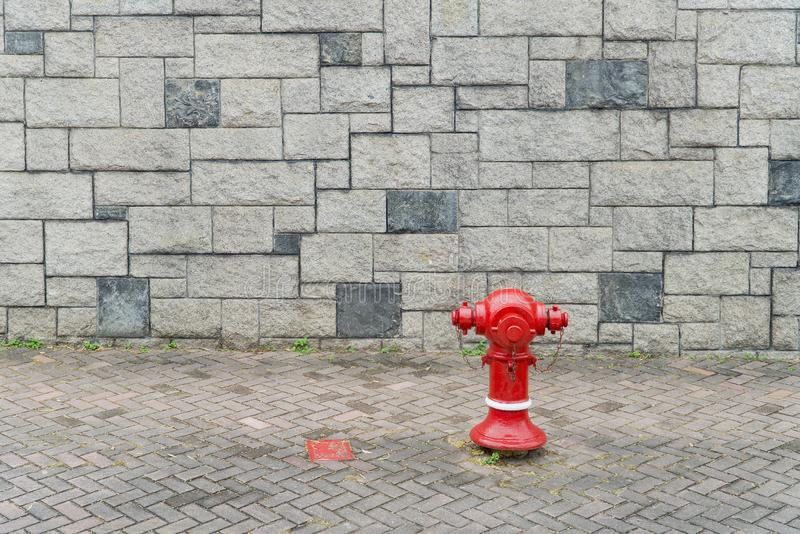 Bakgrund för grå färger för vägg för röd tegelsten för uttag för vatten för brandslang arkivfoto