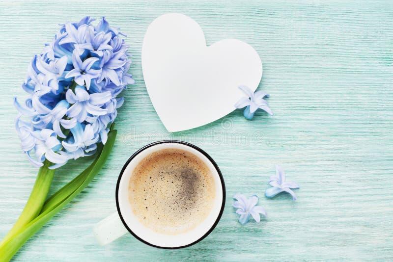 Bakgrund för hälsning för vår för moderdag med hyacintblommor, koppen kaffe och bästa sikt för vit trähjärta Morgonfrukost arkivbild
