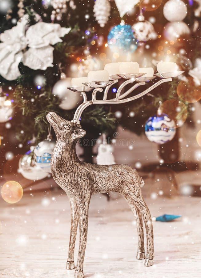 Bakgrund för jul hjortar och julgranmed garneringar, snö, suddigt, gristra som glöder Tema för lyckligt nytt år och Xmas- royaltyfria bilder