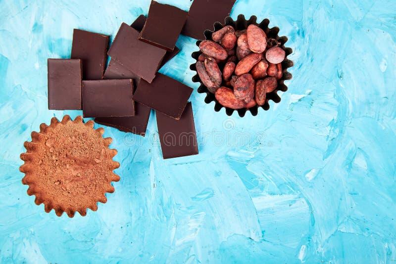 Bakgrund för kakaobönor på blåtttabellen Mörkerchoklad lappar royaltyfri fotografi