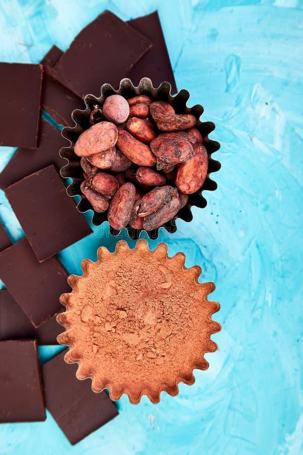 Bakgrund för kakaobönor på blåtttabellen Mörkerchoklad lappar arkivbilder