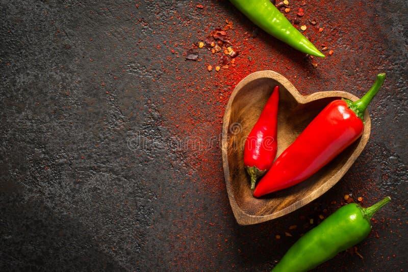 Bakgrund för kryddamatmörker Röd och grön varm peppar i en träbunke arkivbilder