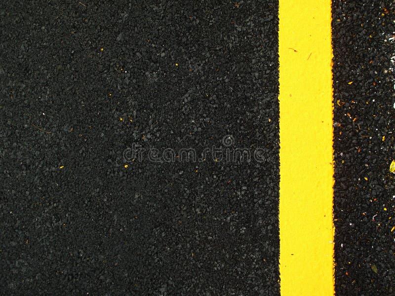 Bakgrund för mörkergrå färgasfalt med guling fodrar arkivbild