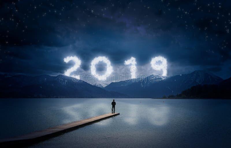 Bakgrund för nytt år, anseende för ung man på en brygga i en sjö och se till bergen under den mörka himlen med molnig text 2019 royaltyfria foton