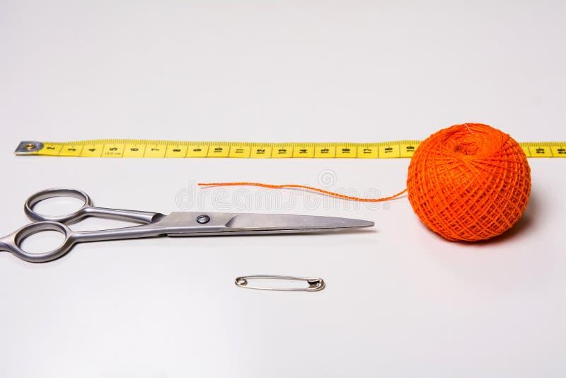 Bakgrund för orange tråd för skräddare och att mäta bandet och sax royaltyfria bilder