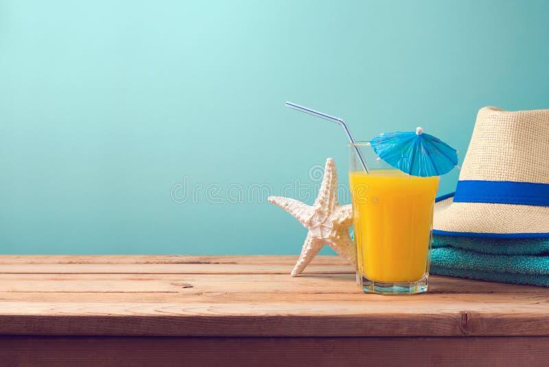 Bakgrund för semester för sommarferie med orange fruktsaft, sjöstjärnan och hatten royaltyfria bilder