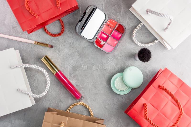 Bakgrund för shopping för bästa sikt för lägenhet lekmanna- med skönhetsmedel och pappers- påsar royaltyfri bild