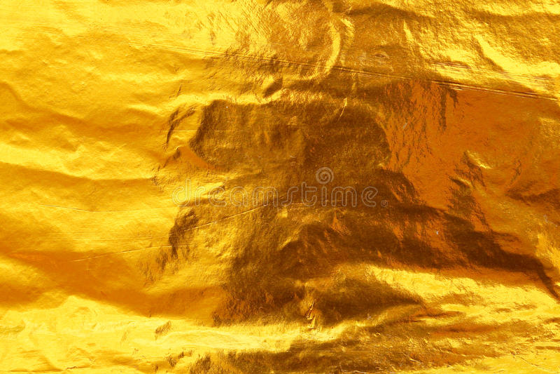 Bakgrund för textur för guld- folie för skinande gult blad mörk royaltyfri foto