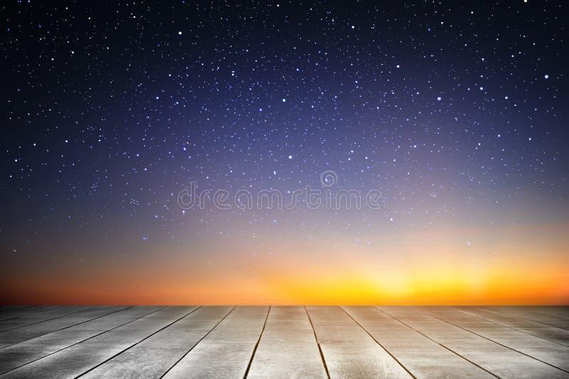 Bakgrund för träplanka och för stjärnklar natt i soluppgångtiden arkivbilder
