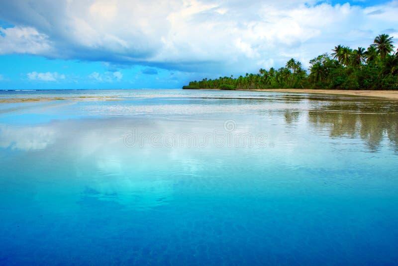 Bakgrund för tropiskt hav och för blå himmel Stora moln reflekteras i vattnet royaltyfri fotografi