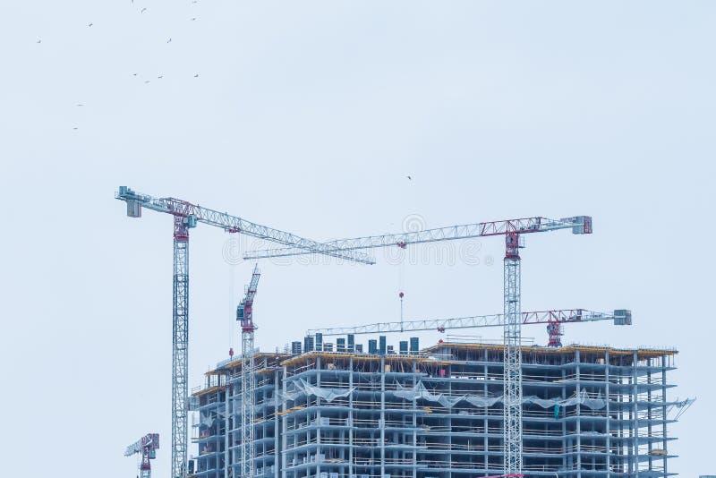 Bakgrund f?r konstruktionsplats Hissa kranar och nya m?ng--v?ning byggnader industriell bakgrund modernt stads- royaltyfria bilder