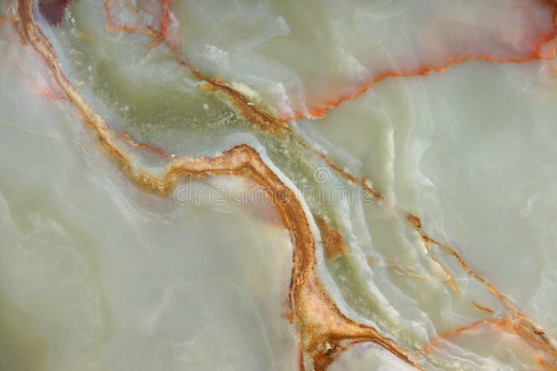 Bakgrund från en modell av en naturlig sten av grön onyx med röda strimmor royaltyfria bilder