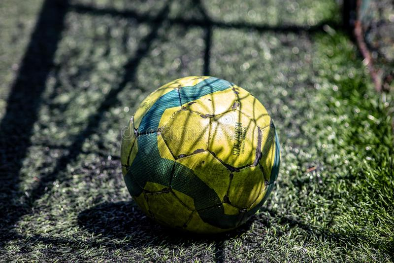 Bakgrund gul och grön fotbollboll på ett syntetiskt fem-en-sida fotbollfält med skuggan av det netto målet arkivfoto