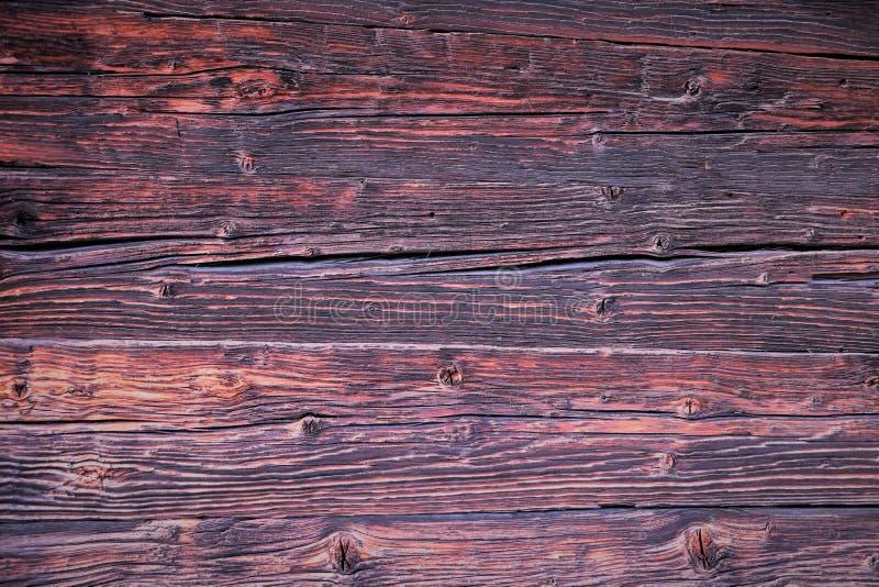 Bakgrund Härliga träbräden, väggen av ett träantikt hus i röda och rosa färgsignaler för brunt, royaltyfri bild