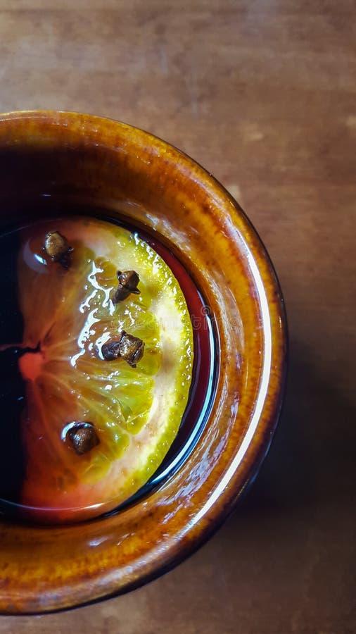 Bakgrund med brunt keramiskt rånar med funderat vin med orange skiva- och nejlikaknoppar royaltyfri foto
