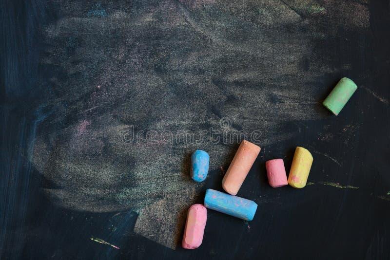 Bakgrund med den färgrika skolan chalks på en svart svart tavla royaltyfri foto